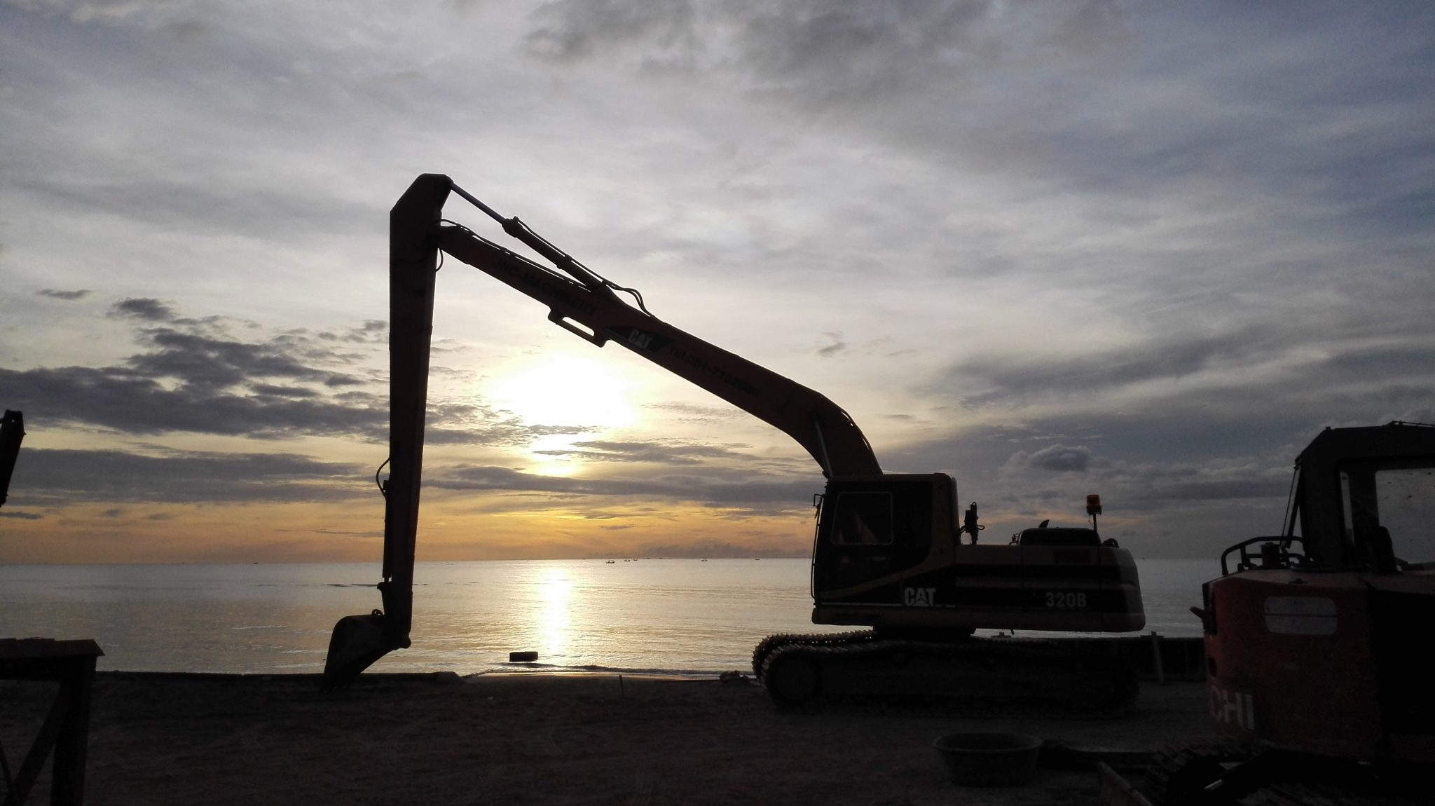 shadow of excavator over sunrise on beach